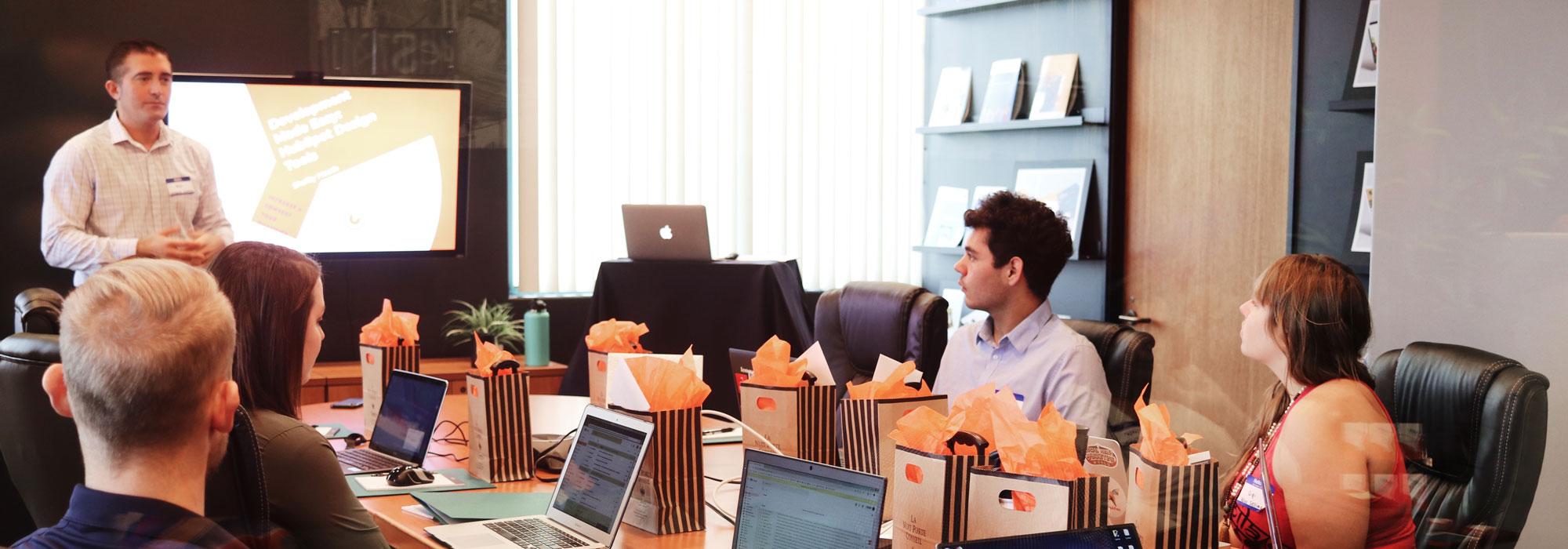 Foto af person der holder oplæg for en gruppe mennesker, med hver deres computer.